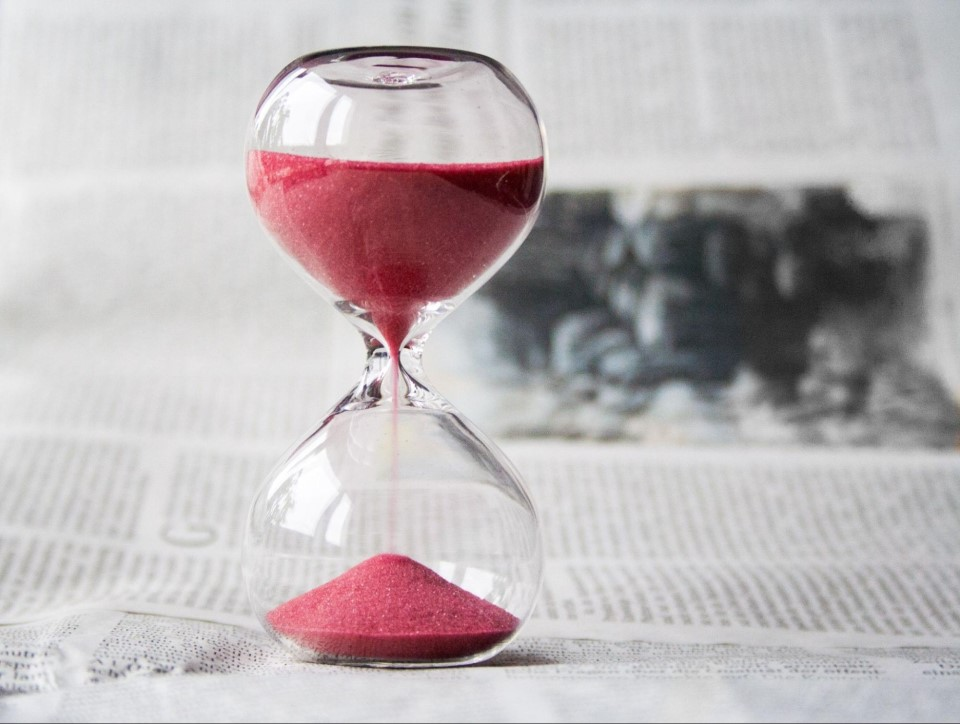 Hourglass with red sand demonstrating time is money in the shipping industry