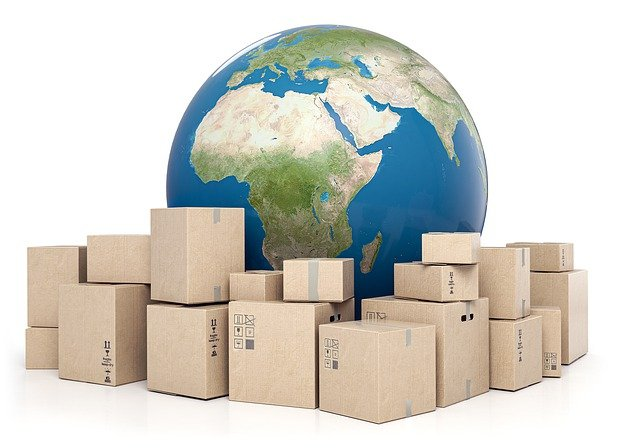 A globe with shipping boxes in front of it.