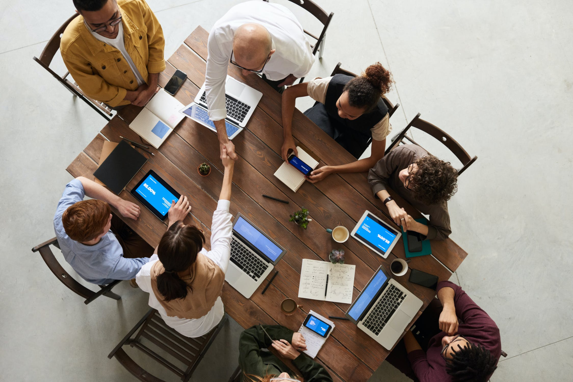 Eight people around a table in a business meeting.