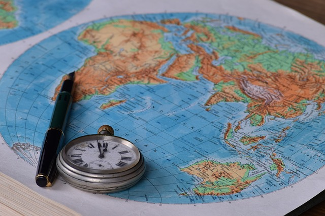 A map of the world with a pen and stopwatch.